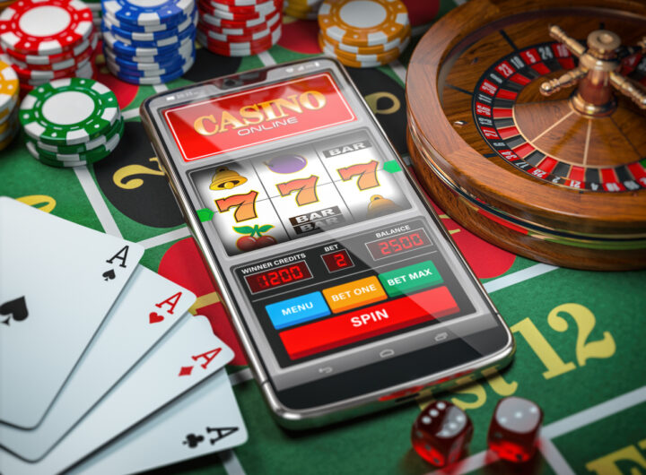 Casino online. Smartphone or mobile phone, slot machine, dice, cards and roulette on a green table in casino. 3d illustration